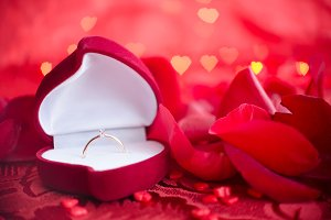 Engagement ring and red rose petals