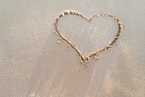 Heart drawn on a sand of beach