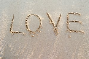 Word LOVE on a sand of beach