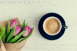 Cup of coffee with bouquet of pink tulips