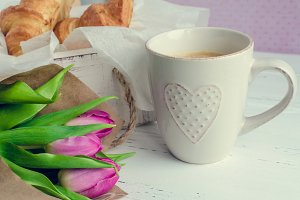Cup of coffee with bouquet of pink tulips and croissants