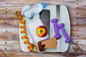 Weight scale, healthy snacks, dumbbells and measuring tape. Healthy eating, diet or weight loss concept