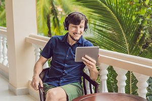 man in tropics talking with friends and family on video call using a tablet and wireless headphones
