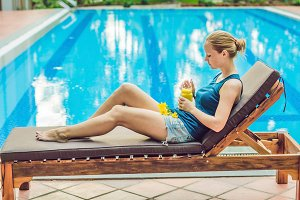 Young woman is holding a smoothie of mango on the background of the pool. Fruit smoothie - healthy eating concept. Close up of detox smoothie with mango