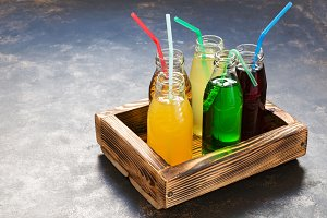 Glass bottles with different juices in a wooden box. The concept of healthy eating.