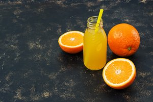 Orange juice in a bottle and half an orange on a dark background.