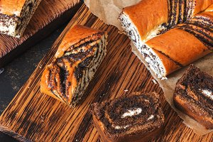 Roll with poppy seeds and roll with cream cut into pieces on a cutting board, top view.