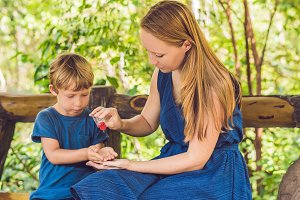 Mother and son using wash hand sanitizer gel in the park before a snack