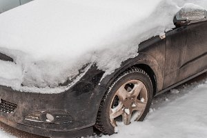 The car in the snow, covered with a white snowdrift.
