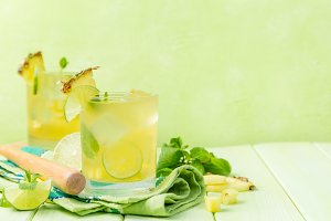 Pineapple and lime drink on rustic background