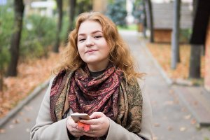 woman in coat walking in autumn Park