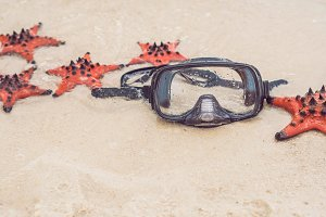 Red starfish and diving mask on the beach