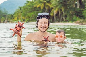Father and son show a red starfish against the backdrop of the sea