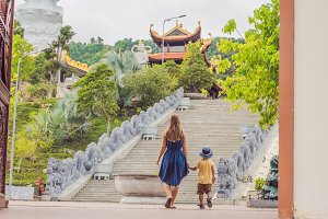Happy tourists mom and son in Pagoda. Travel to Asia concept. Traveling with a baby concept