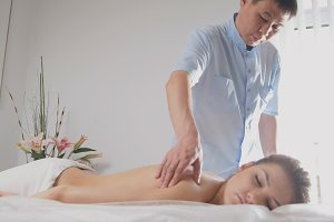 Doctor osteopat and patient - young woman lying on massage table - medical treatment