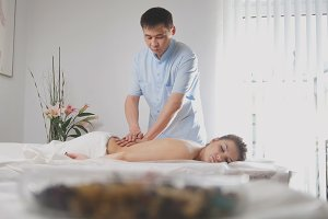 Doctor massagist and patient - young woman lying on massage table - before SPA procedure