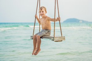 Happy boy sit on swing at the sea shore on sunset