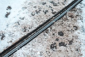 Tram fare in winter in the city. Footprints of pedestrians crossing the metal rails background.