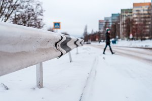 The pedestrian crosses the road in winter in the city on a snow-covered road, traces of wheels on the snow in the city on a zebra.