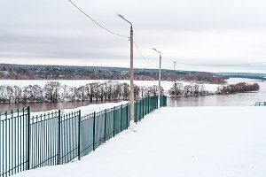 Metal fence in winter in nature, against background of the river, snowy hills, forest landscape in the distance.