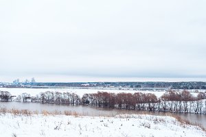 Winter landscape, river against a forest of snow-covered trees. Beautiful winter background in nature. White hills in the distance.