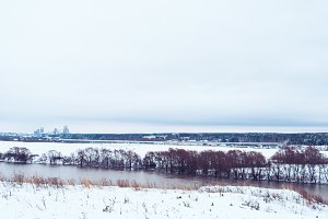 Winter landscape, river against a forest of snow-covered trees. Beautiful winter background in nature. White hills in distance.