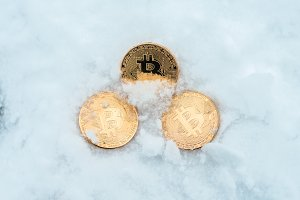 Discarded money. Metal gold coins bitcoin, crypto currency money in winter on snow lie in snowdrift.