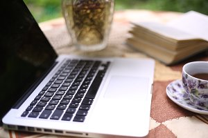 summer working place with laptop vase book and tea cup