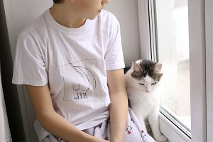 teenage boy in pajama with cat on window sill