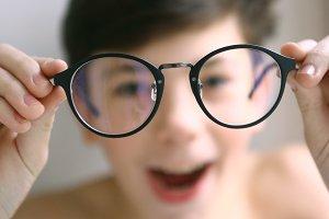teenager kid boy in myopia correction glasses