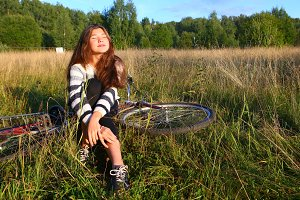 teenager girl sit with  bicycle on the country field