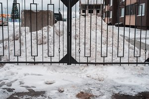 Metal black fence. In winter snow drifts in the parking area. Close to home.