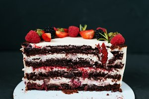 Cut creamy cake on black background, with strawberry raspberries. Dietary white from cream, with chocolate layers of berries.
