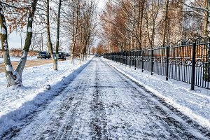 The cleared road in the park, cleaned in winter in the city, the road cleaned by a sunny day. Asphalt in the snow next to the fence.
