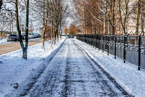 The cleared road in the park, cleaned in winter in the city, the road cleaned by sunny day. Asphalt in the snow next to the fence.