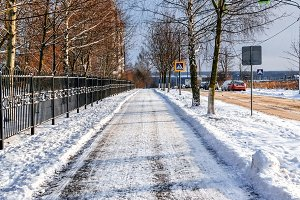 The path is cleaned from snow, in winter the snow is cleared on the asphalt in the city. A cleared road for passers-by.