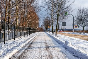 Road in the city in winter, cleaned snow cleaned the street from the snow in the park.
