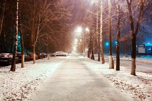 In the winter in city, a night street with phonories, a strong wind of snow. In the park, the road is covered with snow. Storm snow is flying alongside the lamp posts.