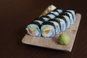 Sushi role on wooden board.