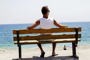 Guy is sitting looking at the sea
