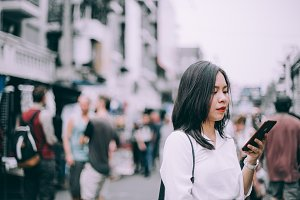 side view of a young woman playing mobile phone on the famous backpacker street Khao San in Bangkok, Thailand