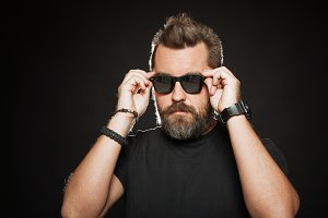 A handsome, strong man with a stylish hairstyle and beard dresses sunglasses in the Studio on a black background. With copy space for your text