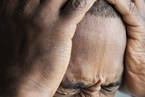 Black man suffering from migraine