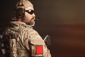 Brutal man in the military desert uniform and body armor is pathetic and looks away at the black background in the Studio. The bearded player in the airsoft safety goggles is holding his rifle