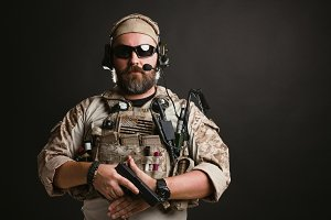 Brutal man in the military desert uniform and body armor stands and holds a gun on a black background in the Studio. The bearded player in the airsoft safety glasses or goggles and active headphones