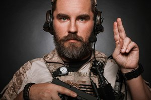 Close-up portrait of brutal bearded man in military desert uniform and body armor who holds his gun on black background. Studio photography of a player in airsoft