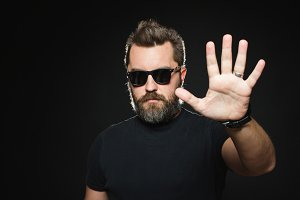 Serious man with beard in a black shirt and sunglasses on a black background in studio. Confident guy standing in front of camera and showing stop signal with his left palm. Copy space for your text