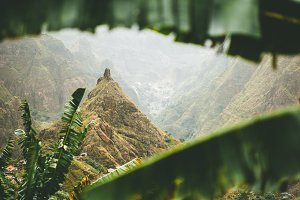 Mountain peak of Xo-xo valley visible throught the banana lleaves frame down the valley. One of the best trekking route on Santo Antao island, Cape Verde. Cloudy weather