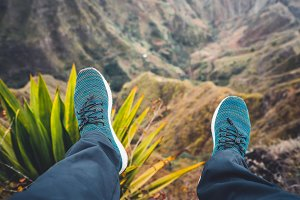 Feet of traveler streching down his legs over breathtaking mountain landscape with mountain peaks, rugged cliffs on Santo Antao Island, Cape Verde. Agave underneath