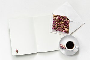 Dry roses in envelope and cup of tea with empty open copy book for text on white background, flat lay, overhead view,